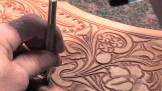 The thumbprint tool in leather carving a saddle